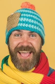 Uomo allegro con barba e baffi che indossa sciarpa alla moda e cappello moda invernale maschile bello