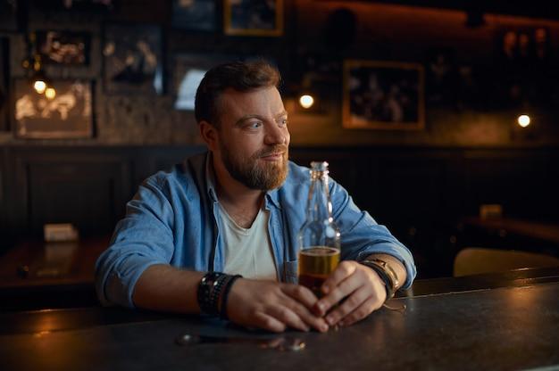Uomo allegro con una bottiglia di birra seduto al bancone del bar