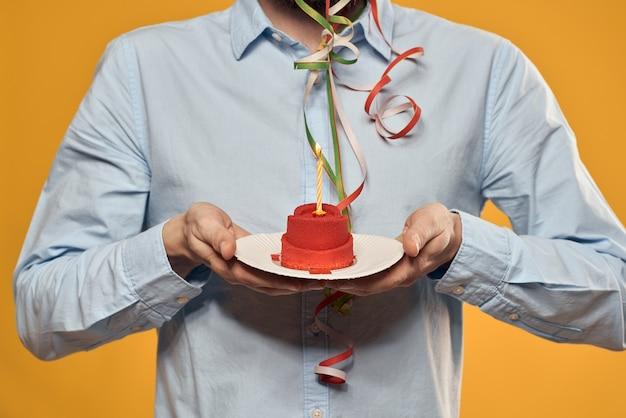 Uomo allegro con una torta su una protezione di feste di compleanno della parete gialla