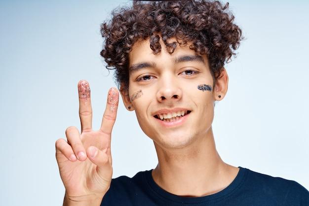 Uomo allegro con cosmetici per capelli ricci sulla pelle pulita del viso