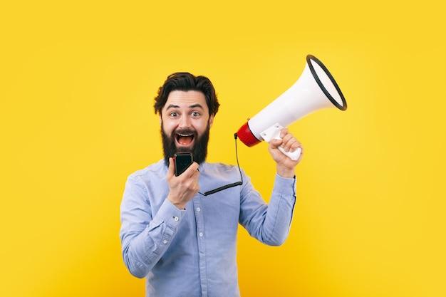 Uomo allegro con il megafono sopra la parete gialla, concetto di successo