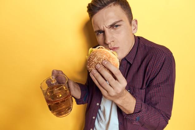Uomo allegro con un boccale di birra e un hamburger sulle sue mani parete gialla stile di vita alimentare dieta