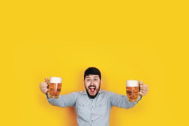 Uomo allegro con due bicchieri di birra, immagine sul muro giallo alla moda