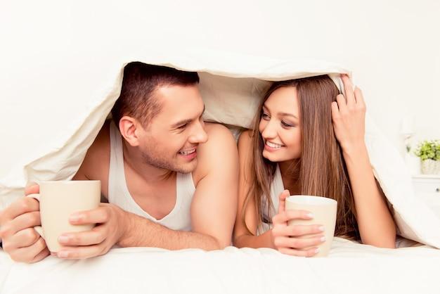 Allegro uomo e donna crogiolarsi con coperta e tè caldo