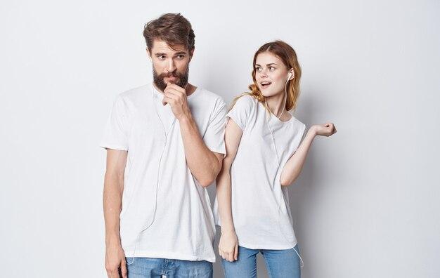Allegro uomo e donna in cuffie ascoltando musica e balli su sfondo grigio vista ritagliata