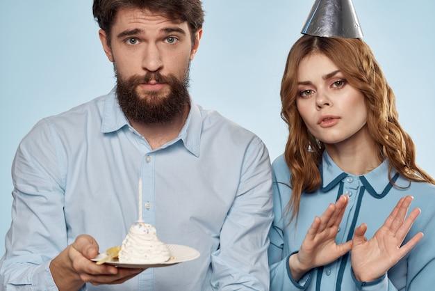 Uomo allegro e donna con la torta in una priorità bassa blu del partito corporativo del piatto
