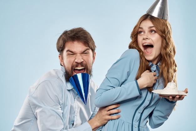 Uomo allegro e donna con la torta in una parete blu del partito corporativo del piatto.