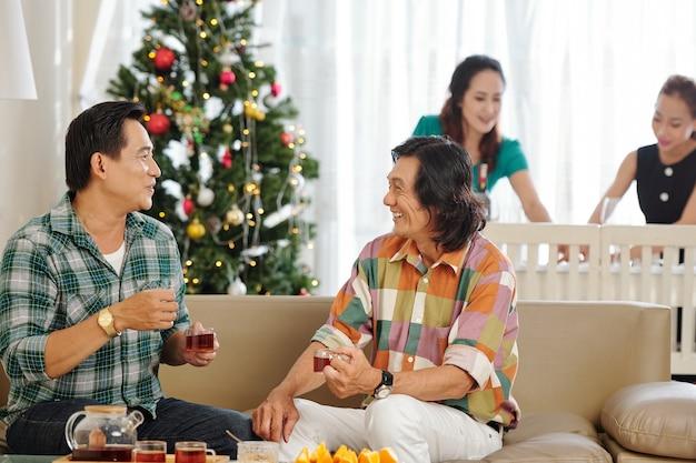 Uomini asiatici maturi allegri che bevono tè e discutono di notizie quando le loro mogli servono il tavolo di natale
