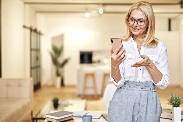 Allegra imprenditrice matura con gli occhiali che fa una videochiamata online utilizzando lo smartphone in piedi