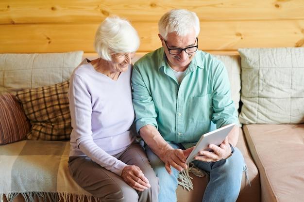Allegro maturo marito e moglie utilizzando la chat video durante la comunicazione con gli amici o la famiglia mentre è seduto sul divano