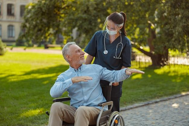 Uomo maturo allegro in sedia a rotelle che sorride alla giovane infermiera premurosa che indossa visiera e maschera