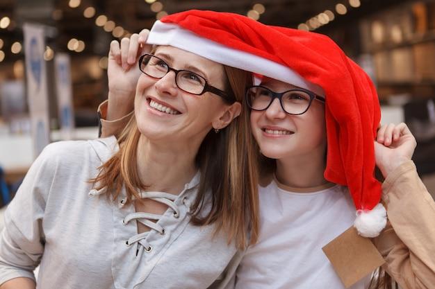 Allegra donna matura e sua figlia adolescente ridendo, indossando il cappello di babbo natale