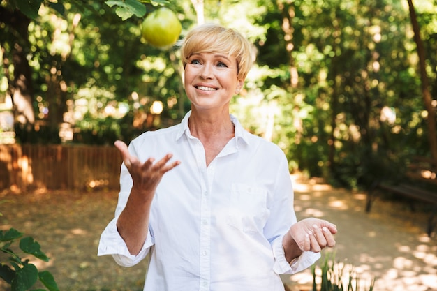 Donna matura allegra che tiene mela verde