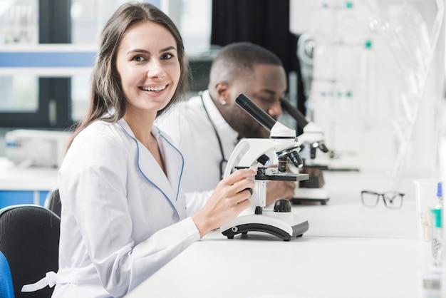 Donna allegra del medico al microscopio
