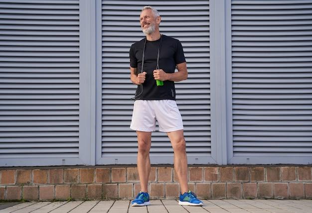 Allegro uomo atletico di mezza età in abbigliamento sportivo che sorride da parte mentre tiene la corda per saltare in piedi