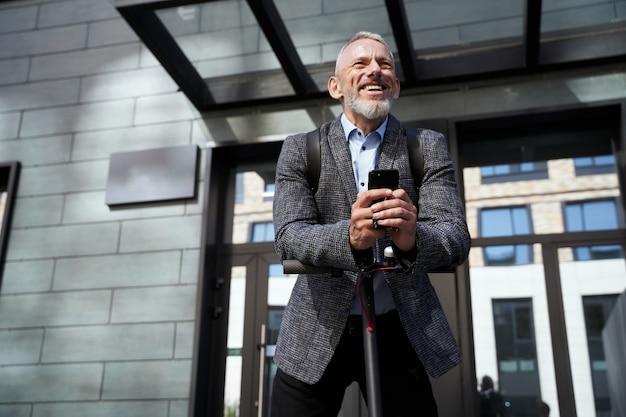Allegro uomo d'affari di mezza età che sorride tenendo in mano il suo telefono cellulare mentre sta in piedi con l'elettrico