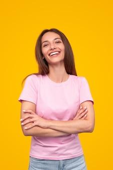 Allegra femmina millenaria in abito casual con le braccia incrociate guardando la fotocamera e ridendo allegramente su sfondo giallo brillante