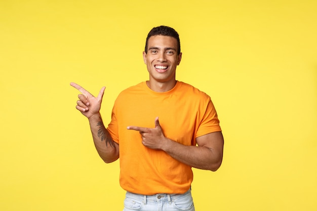 Allegro uomo moderno con braccio tatuato, che punta a sinistra come promozione del negozio online, invita gli ospiti a partecipare alla festa, sorridendo con gioia, consiglia di provare qualcosa, dare consigli su quale luogo visitare, sfondo giallo