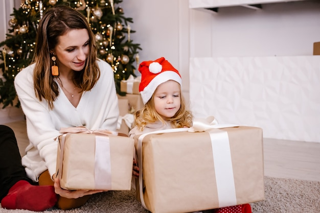 La mamma allegra dà un regalo di natale a sua figlia carina. genitore e bambino che hanno divertimento vicino all'albero al chiuso.