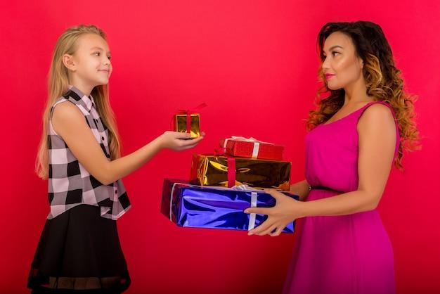 Mamma allegra e la sua ragazza carina figlia che tengono regalo presente. sfondo rosso