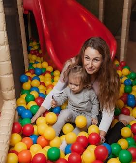 Mamma allegra e piccola figlia stanno giocando in piscina con palline colorate nel centro di intrattenimento per bambini. vacanza in famiglia