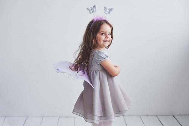Stato d'animo allegro e sorriso sincero. bella bambina in costume da fata in piedi nella stanza.