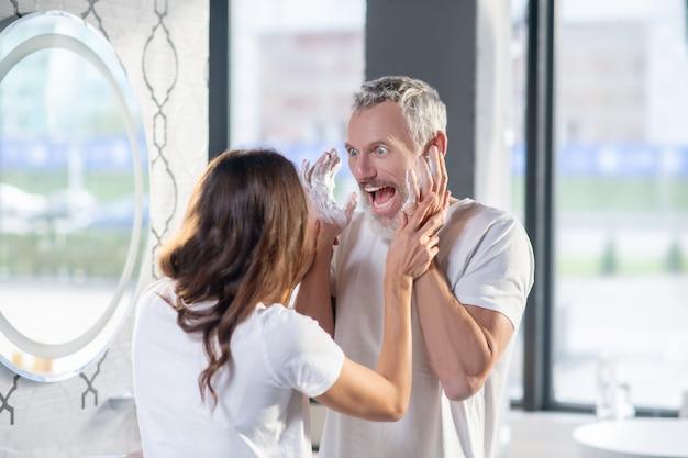 Mattina allegra. smorfie allegro marito barbuto con le mani alzate in schiuma saponosa e moglie che lo tocca