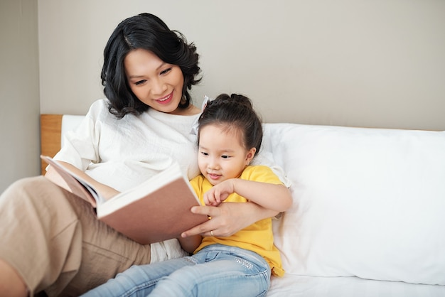 Madre allegra e la sua piccola figlia che leggono un libro insieme