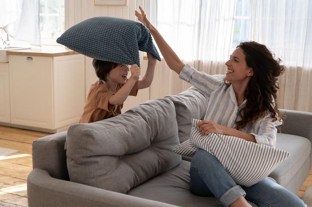 Madre allegra con bambini in età prescolare combattono cuscini in soggiorno divertenti attività familiari a casa su