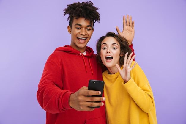 Allegro multhiethnic coppia adolescente in piedi insieme isolato, prendendo un selfie
