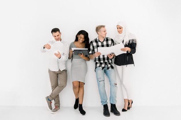 Gente di affari o studenti professionale multirazziale allegra che sorride e che parla insieme stando sul fondo bianco della parete