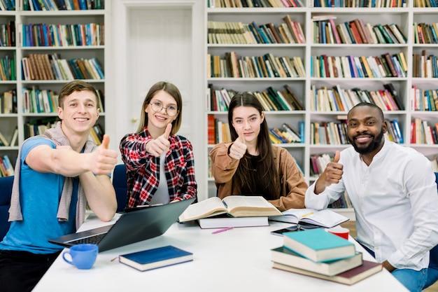 Allegri studenti multirazziali, due ragazzi e due ragazze, seduti al tavolo con libri e laptop nella sala di lettura della biblioteca, guardando la telecamera e mostrando il segno ok
