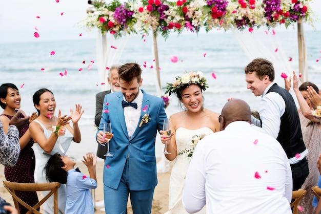 Sposi novelli allegri al cerimoniale del matrimonio in spiaggia