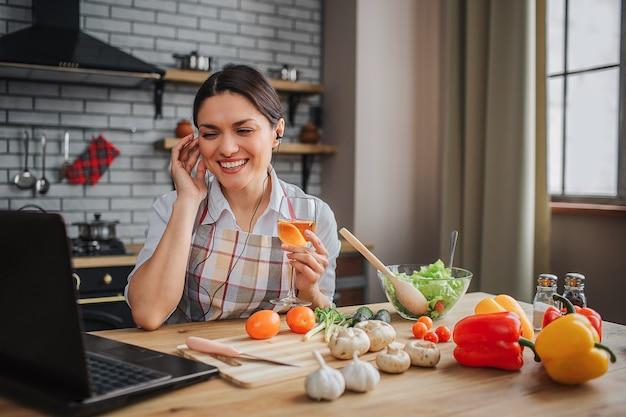 La donna attraente piacevole allegra si siede al tavolo in cucina