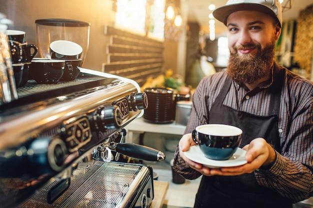 Barista allegro e piacevole che tiene tazza di caffè in mano. sta in cucina alla macchina del caffè.