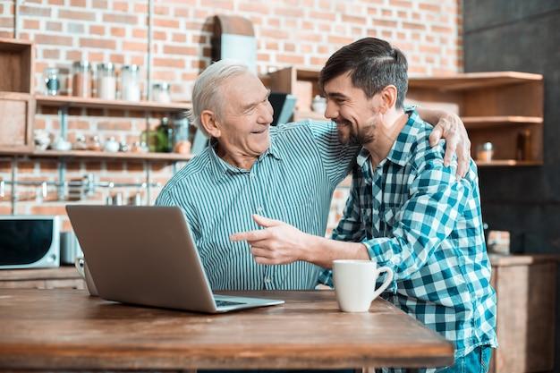 Allegro simpatico uomo anziano sorridendo e abbracciando suo figlio mentre impara a usare un computer portatile