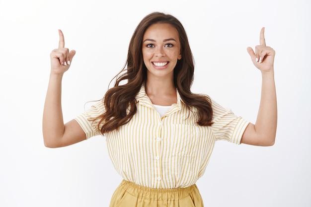 Il responsabile del servizio clienti femminile allegro presenta volentieri il prodotto, aiuta a trovare lo spazio per la copia, punta le dita in alto, sorride a trentadue denti con un'espressione soddisfatta ed eccitata, felice di mostrare un fantastico promo