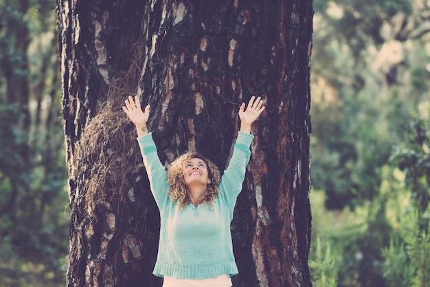 Allegra bella donna graziosa in piedi con un grosso tronco d'albero in scena