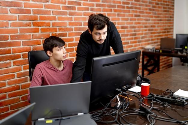 Gli impiegati allegri sono seduti vicino al tavolo e guardano la telecamera. interiore dell'ufficio moderno. concetto di affari.
