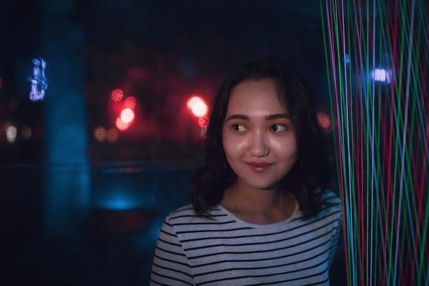 Allegro ottimista ragazza asiatica sorridente notte ritratto luce al neon sfondo