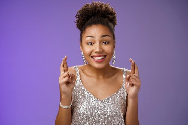 Allegro ottimista affascinante ragazza afroamericana che sostiene l'amico esprimi il desiderio di vincere il primo premio incrociare le dita fortuna sorridendo ampiamente indossa un abito scintillante d'argento anticipando la buona fortuna.