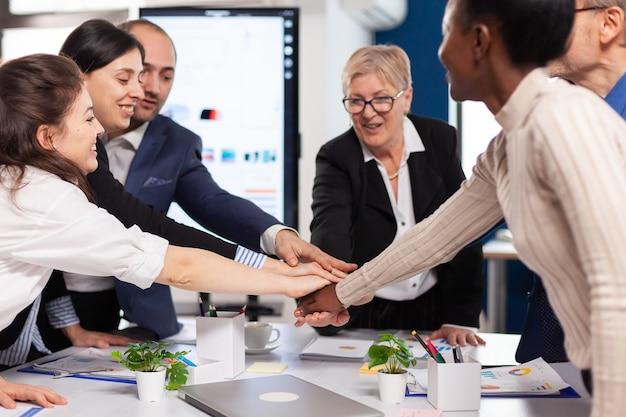 Allegri uomini d'affari felicissimi nella sala conferenze che celebrano diversi colleghi con nuove opportunità che si godono l'incontro di vittoria nell'ufficio di un'ampia sala.