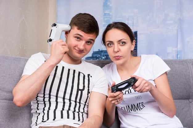 Coppia allegra che gioca al videogioco mentre il ragazzo si gratta la testa davanti alla console seduto sul divano di casa