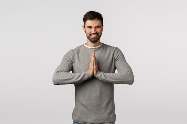 Istruttore di yoga maschio adulto allegro e pacifico che insegna come liberare lo stress, inchinando il gesto del namaste, tenendo le mani premute insieme sul petto, pregando, sorridendo felice, chiedendo aiuto o ringraziando