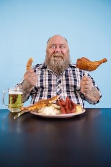 La persona allegra con sovrappeso si siede a tavola con cibo grasso e birra