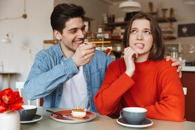 Foto allegra di una giovane coppia di 20 anni che si siede nella caffetteria e uomo donna che allatta con una gustosa torta