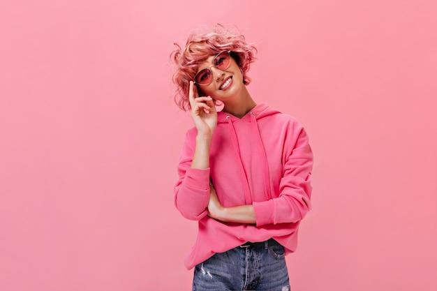 La donna allegra dai capelli rosa in felpa oversize con cappuccio e pantaloni di jeans sorride ampiamente