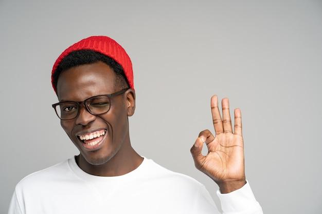Allegro giocoso uomo afroamericano di buon umore ammiccante, mostrando il gesto giusto