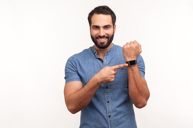 Allegro uomo positivo con la barba in camicia blu che punta all'orologio da polso a portata di mano e sorridente, mostrando il nuovo orologio intelligente, controllando gli indicatori. colpo dello studio dell'interno isolato su priorità bassa bianca