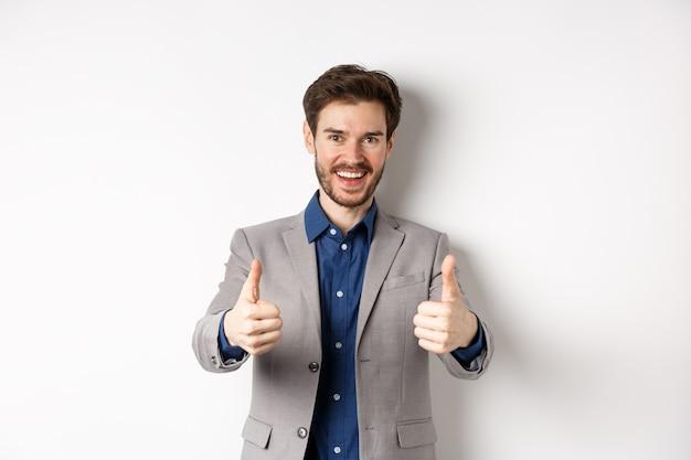 Giovane allegro e positivo in giacca e cravatta che mostra i pollici in su e sorridente, come qualcosa di buono, elogia il buon lavoro, in piedi felice su sfondo bianco.